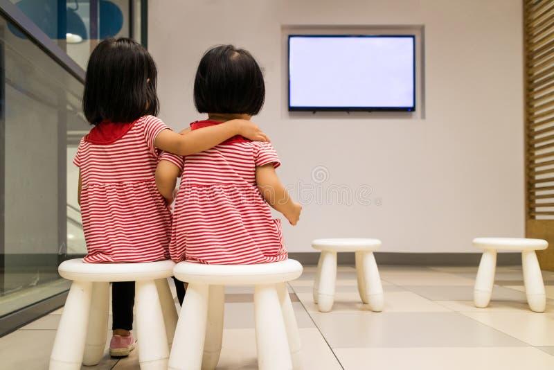 Азиатская китайская маленькая сестра 2 смотря ТВ стоковые изображения rf