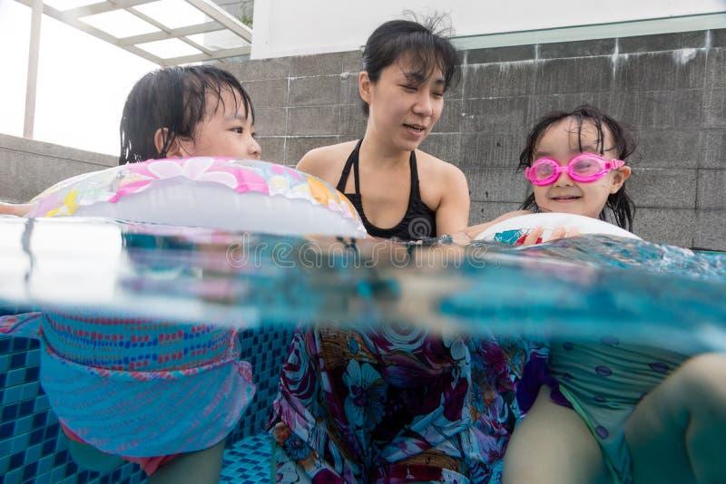 Азиатская китайская семья играя на открытом бассейне стоковое фото