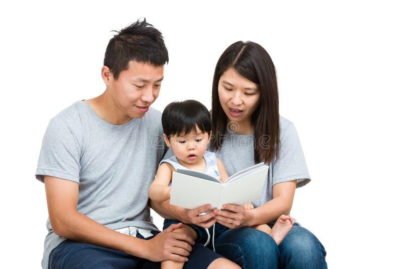 Азиатская книга чтения семьи совместно стоковая фотография