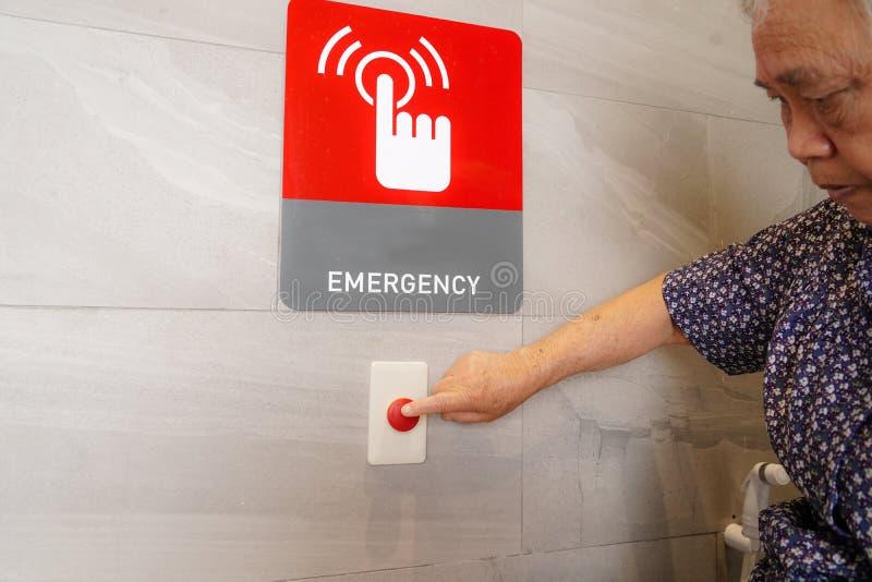 Азиатская кнопка старшей или пожилой прессы женщины пожилой женщины терпеливой аварийная в особенном bathroom туалета для беремен стоковые фотографии rf