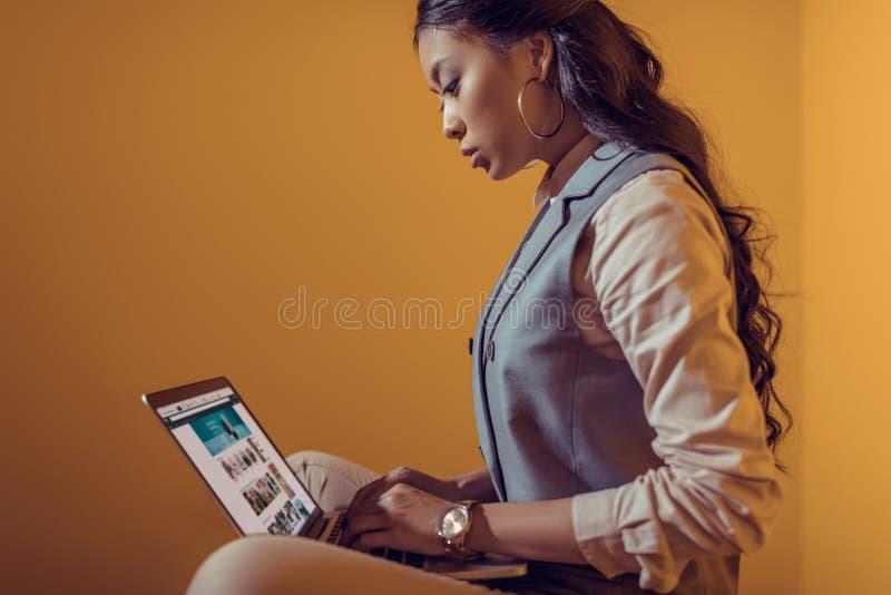 азиатская коммерсантка используя компьтер-книжку с вебсайтом Амазонки перед стоковое фото rf