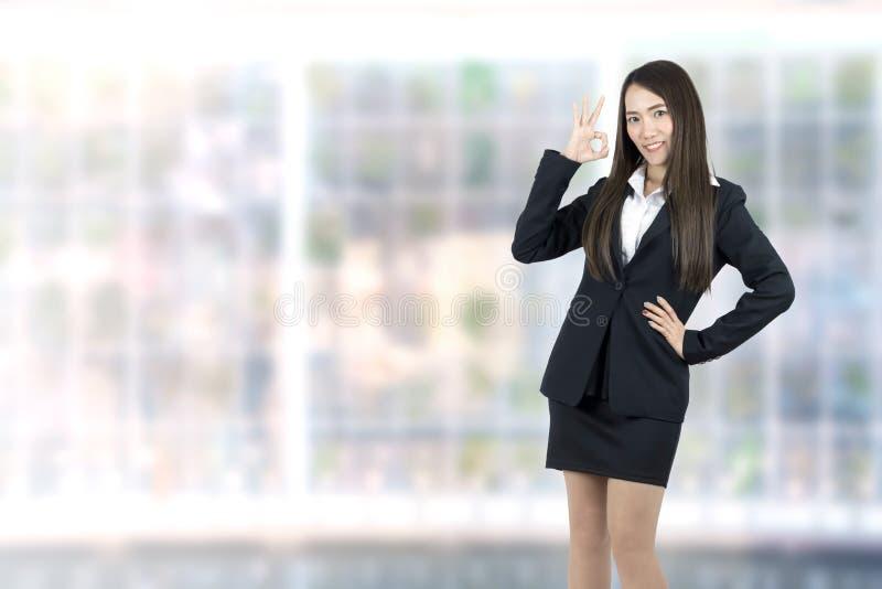 Азиатская коммерсантка показывая ОДОБРЕННЫЙ усмехаться знака руки счастливый в предпосылке офиса стоковые изображения rf