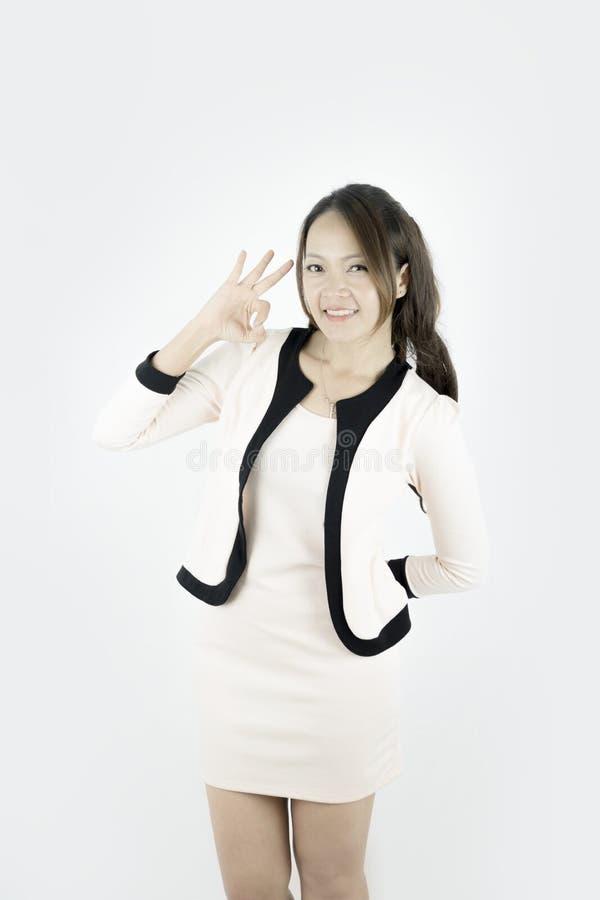 Азиатская коммерсантка показывая ОДОБРЕННЫЙ усмехаться знака руки счастливый стоковые фото
