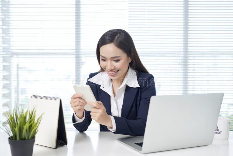Азиатская коммерсантка сидя столом с ноутбуком и используя чернь в офисе стоковая фотография rf
