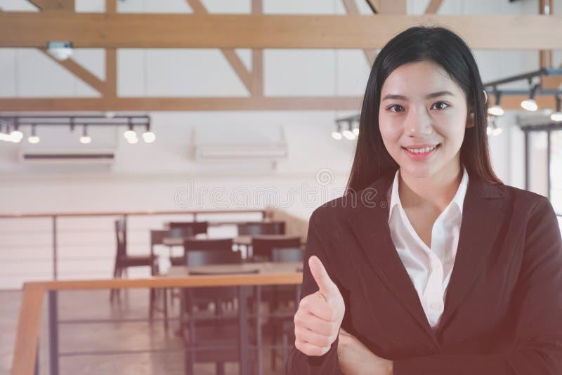 Азиатская коммерсантка усмехаясь на камере уверенно wea молодой женщины стоковые фото
