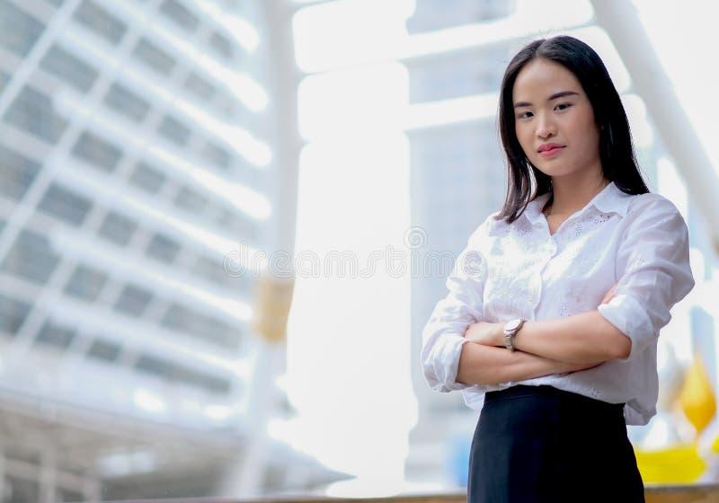 Азиатская красивая девушка дела с белым поступком рубашки как уверенный и стойка среди высокого здания в большом городе во времен стоковая фотография rf