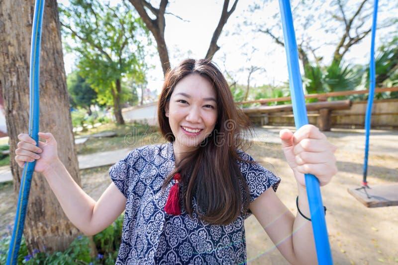 Азиатская красивая девушка имеет игру качания с предпосылкой природы в morming на провинции Nan, Таиланде стоковое изображение