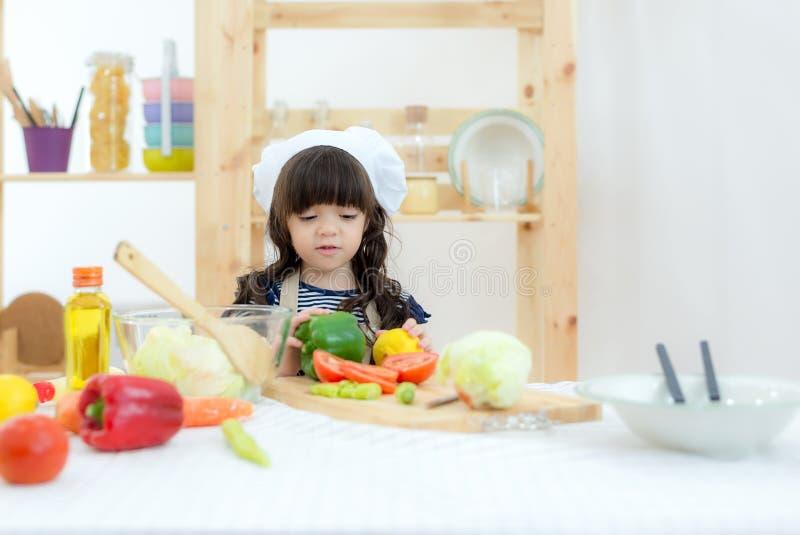 Азиатская красивая девушка ребенк варя и режа овощи на кухне, поэтому счастливый и ослабить для еды повара полагаться и образован стоковые фотографии rf