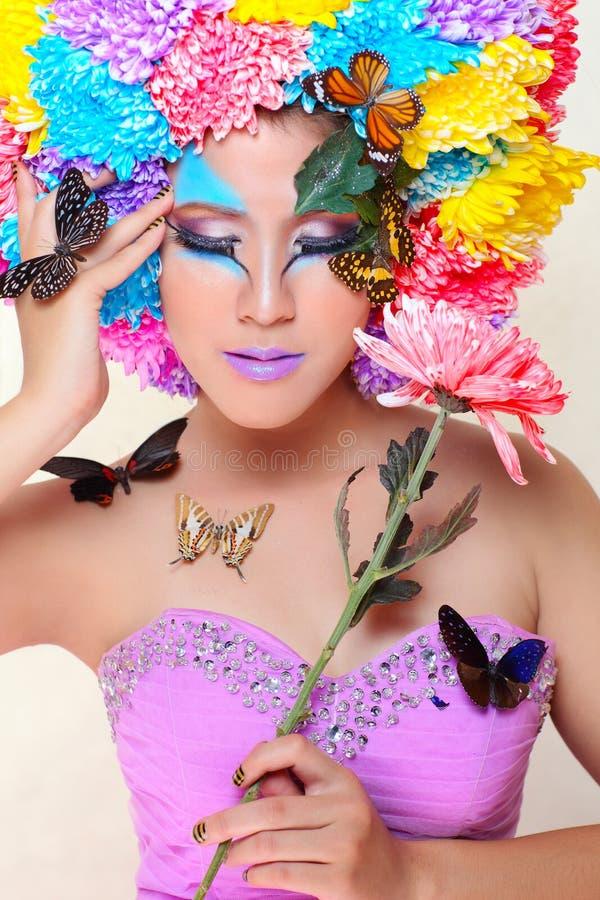 Азиатская красивая девушка с красочным составляет с свежими цветками и бабочкой хризантемы стоковое фото