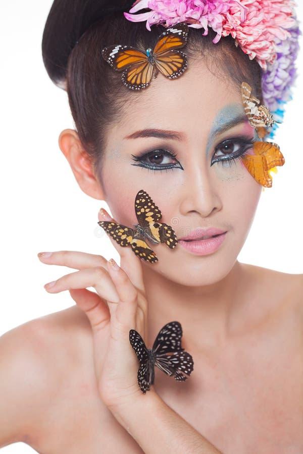 Азиатская красивая девушка с красочным составляет с свежими цветками и бабочкой стоковые изображения