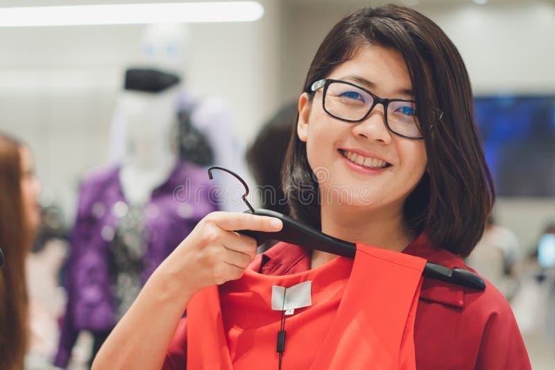 Азиатская красивая женщина выбирает купить новый набор соответствующий на сезон, сезон согласно времени, концепции моды, покупкам стоковое фото