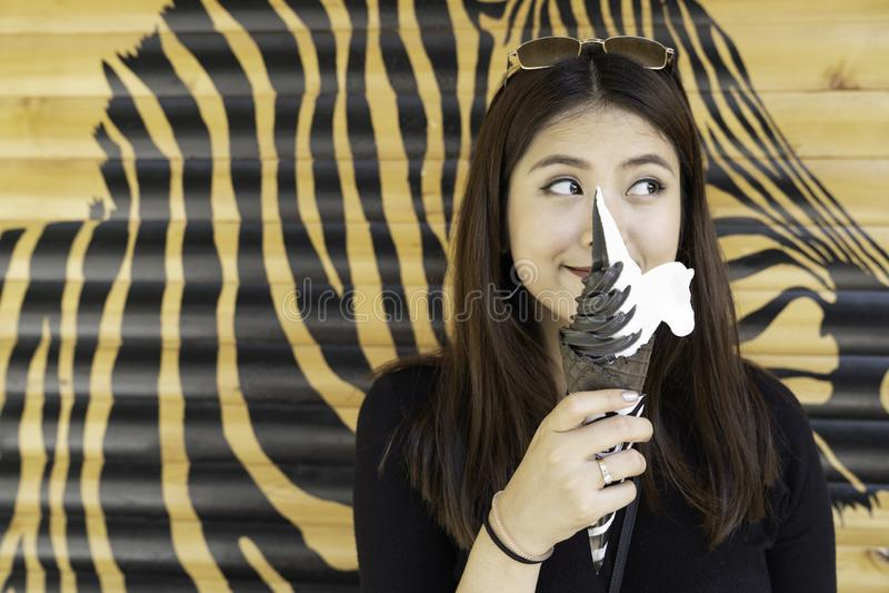 Азиатская красивая женщина наслаждается конусом мороженого стоковое фото rf