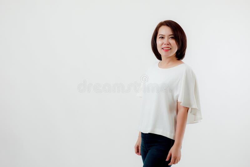 Азиатская красивая женщина нося белую рубашку, стоя усмехающся счастливо с белой предпосылкой стоковые фото