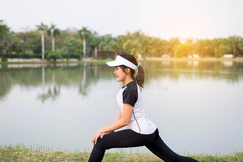 Азиатская красивая женщина протягивая и нагревая перед бегом или разминкой на общественном парке стоковое изображение