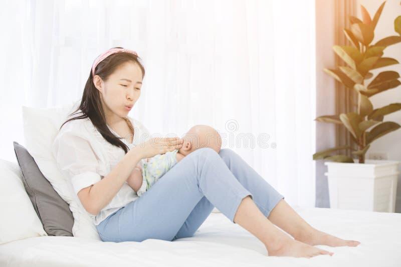 Азиатская красивая мама играя с ее младенцем стоковая фотография