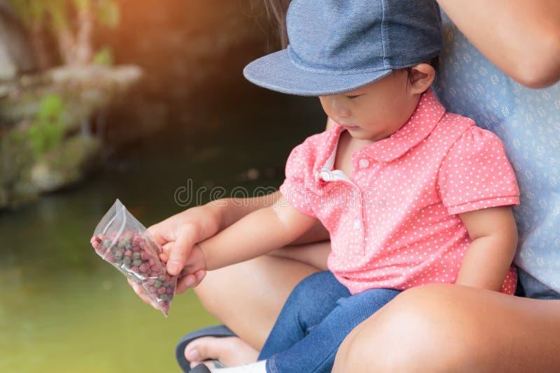 Азиатская красивая мать принимает заботе ваших рыб милого младенца подавая стоковые фото