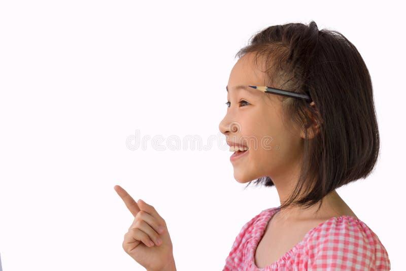Азиатская маленькая девочка думая с карандашем за ее ухом, хорошие идеи для работы, творческих способностей, аналитических, Ребен стоковая фотография rf