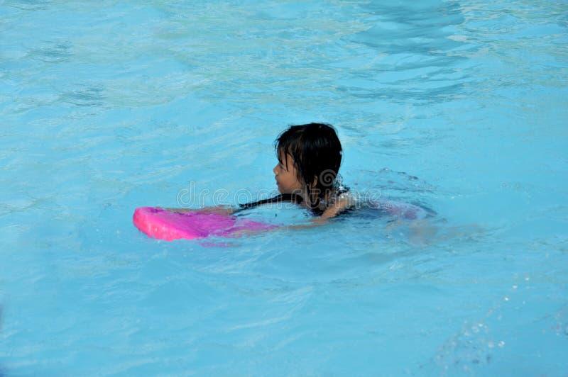 Азиатская маленькая девочка играя в бассейне стоковая фотография rf