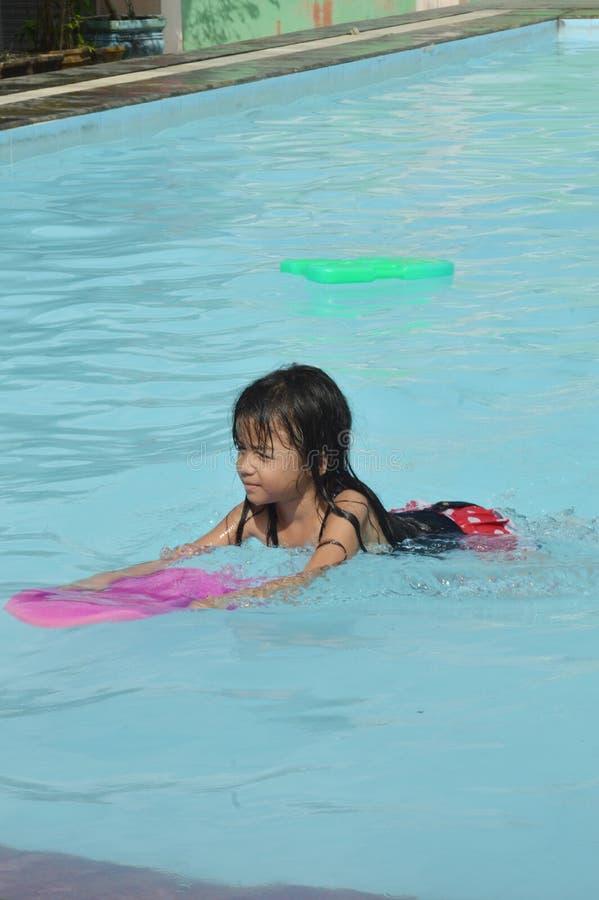 Азиатская маленькая девочка играя в бассейне стоковые изображения