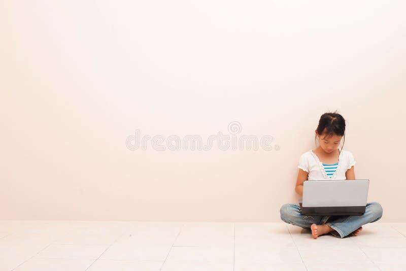 Азиатская маленькая девочка используя ноутбук против розовой предпосылки стоковое изображение rf