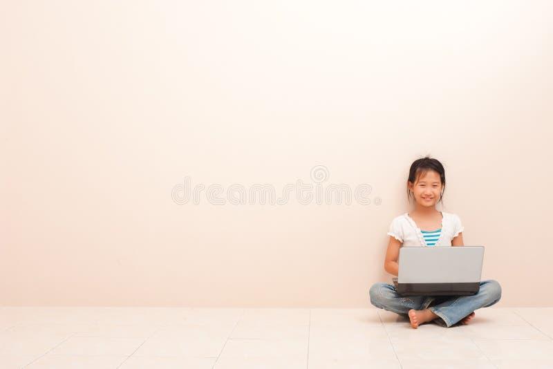 Азиатская маленькая девочка используя ноутбук, смотрящ камеру и усмехающся против розовой предпосылки стоковые изображения rf