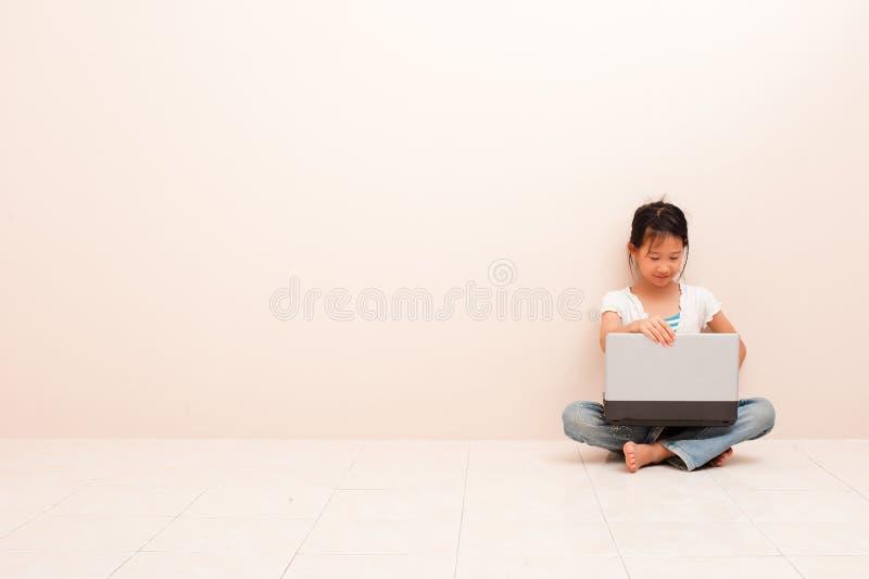 Азиатская маленькая девочка используя ноутбук, смотрящ экран и усмехающся против розовой предпосылки стоковые изображения