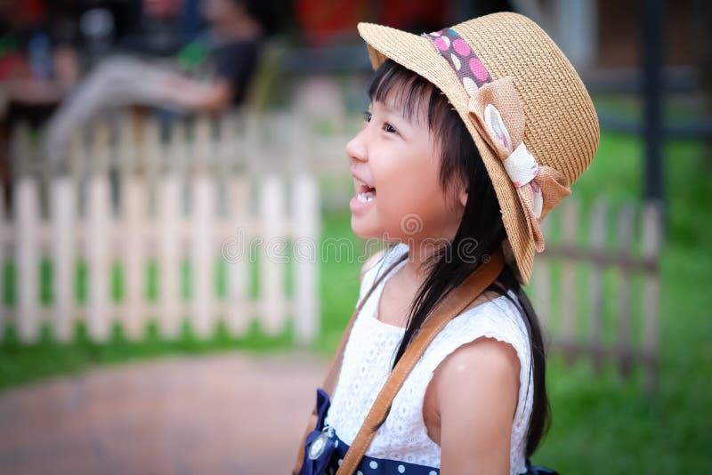 Азиатская маленькая девочка наблюдая его деятельность вперед и смеяться над стоковое изображение rf