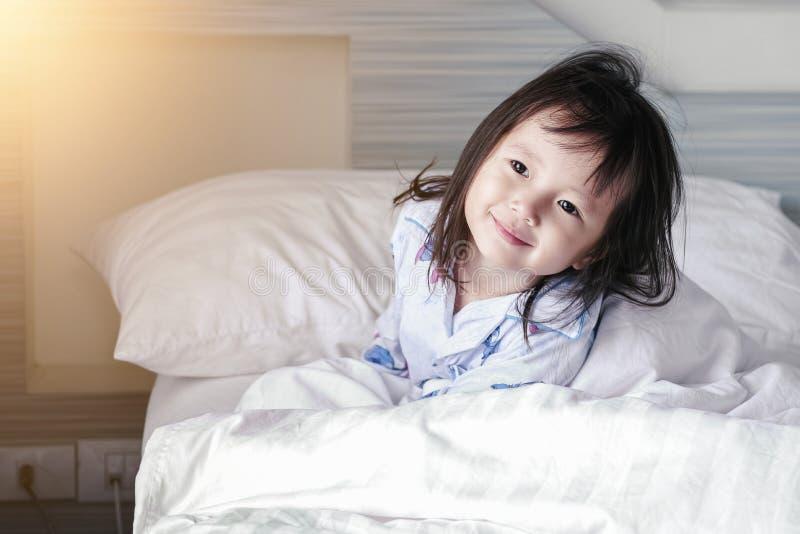 Азиатская маленькая девочка просыпает вверх от сна Доброе утро дома стоковая фотография