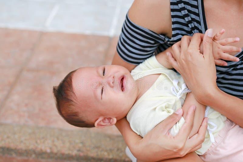 Азиатская мать держа кричащий newborn ребенка стоковая фотография rf