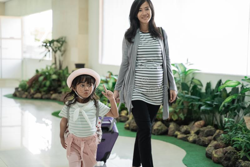 Азиатская мать и ее дочь шли вверх и вытянули чемодан стоковое фото