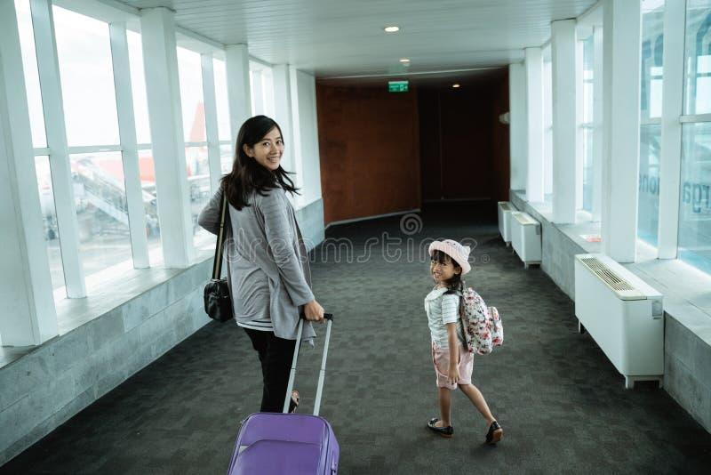 Азиатская мать и ее дочь шли вверх и вытянули чемодан стоковая фотография