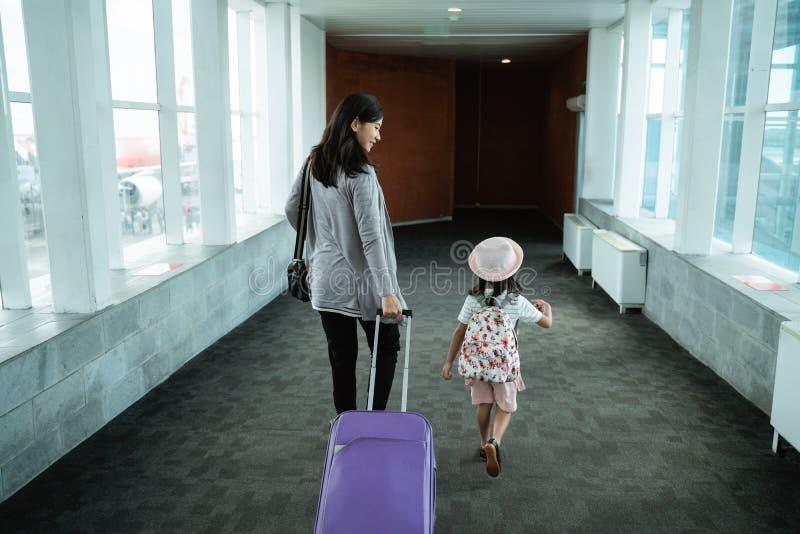 Азиатская мать и ее дочь шли вверх и вытянули чемодан стоковые изображения