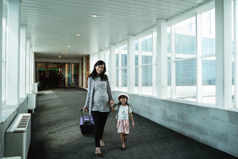Азиатская мать и ее дочь шли вверх и вытянули чемодан стоковые фотографии rf