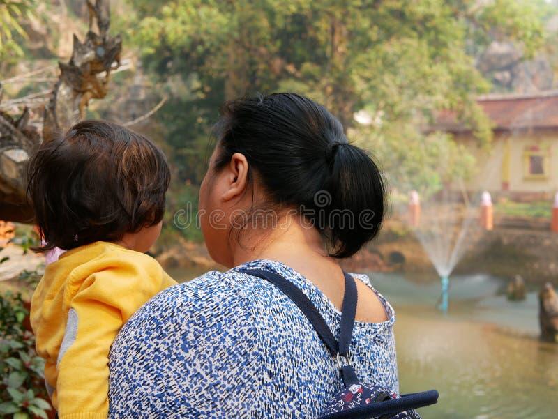 Азиатская мать, несущая/удерживающая свою малышку, чтобы показать ей лРстоковая фотография