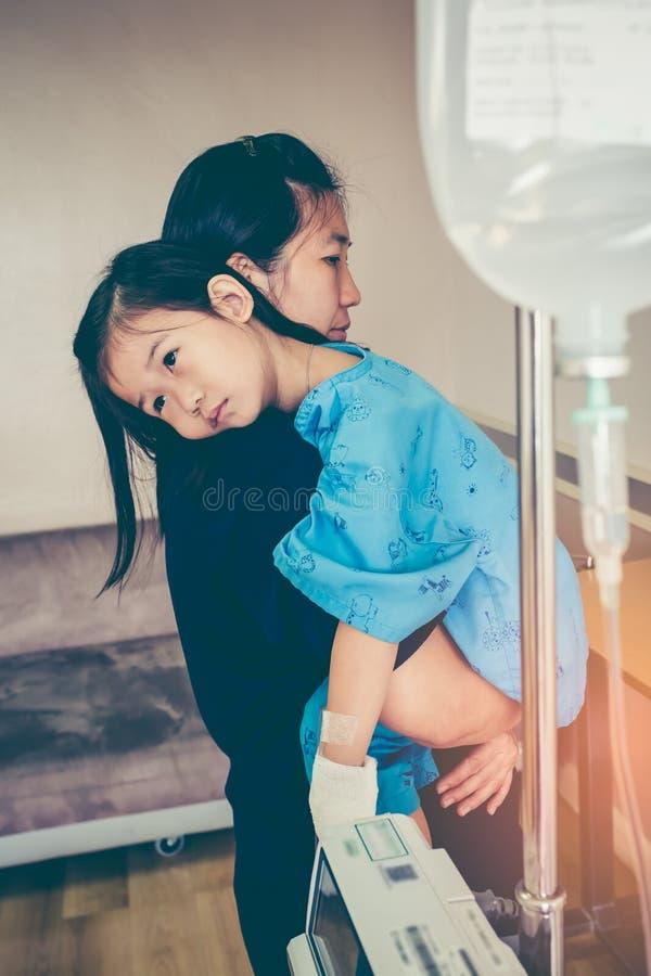 Азиатская мать нося ее дочь, соляной потек IV на ` s ha ребенка стоковое изображение rf