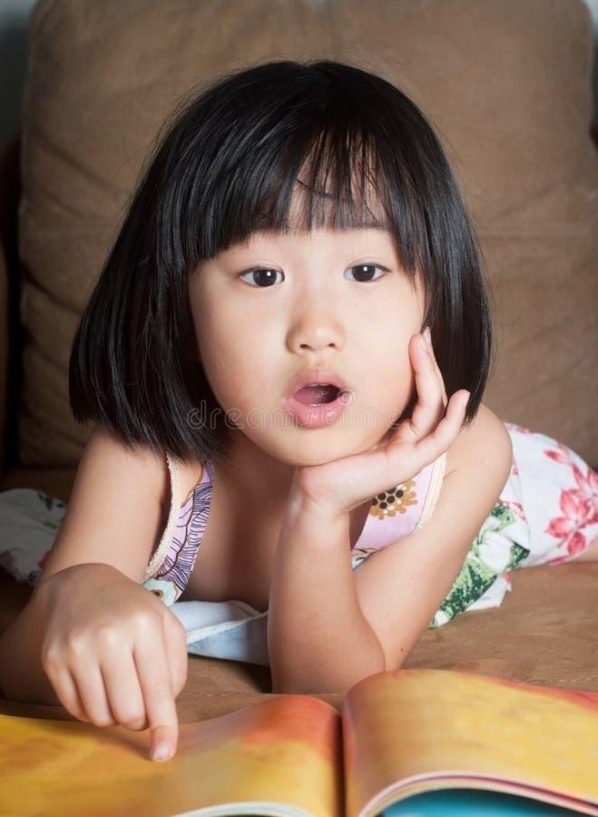 Азиатская маленькая девочка прочитала ее книгу aloud стоковая фотография rf