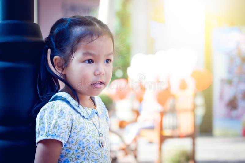 Азиатская маленькая девочка стоя и смотря в парке стоковая фотография