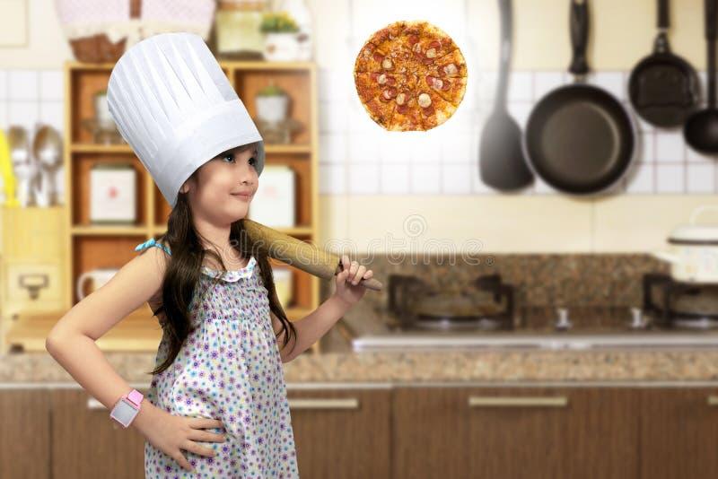 Азиатская маленькая девочка с вращающей осью думая для того чтобы сделать пиццу стоковые фотографии rf