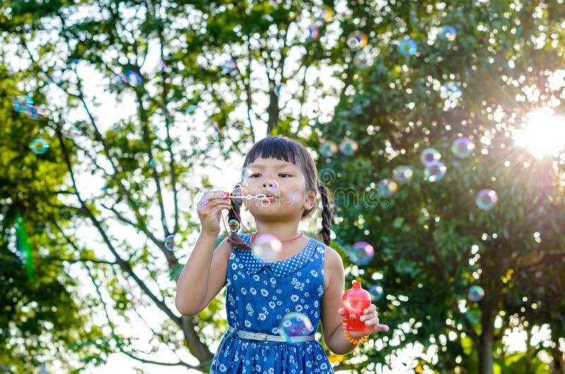 Азиатская маленькая девочка дует пузыри мыла стоковое изображение rf