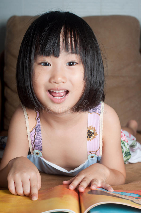 Азиатская маленькая девочка читая ее книгу стоковые изображения rf