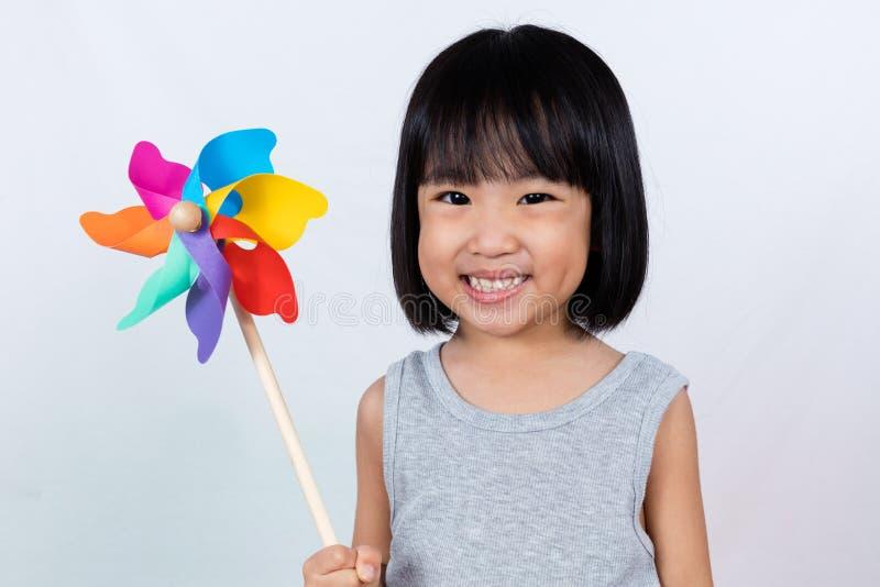 Азиатская маленькая китайская девушка играя красочный Pinwheel стоковое фото