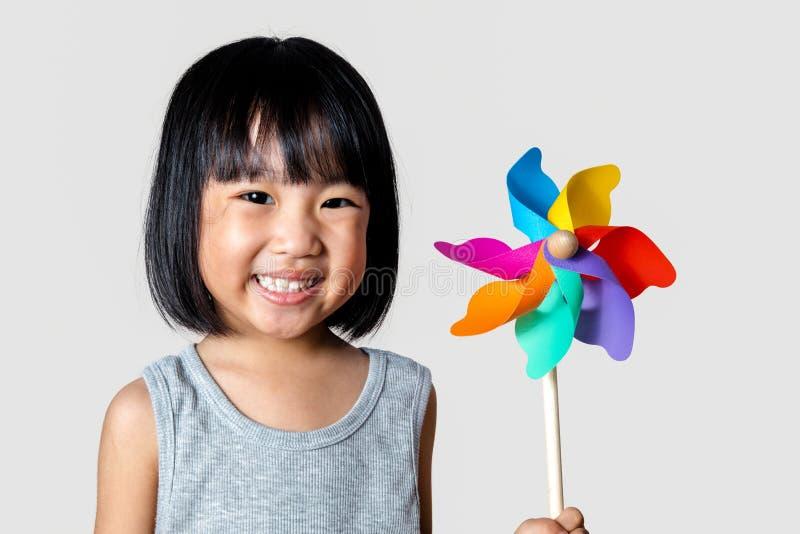 Азиатская маленькая китайская девушка играя красочный Pinwheel стоковое фото rf
