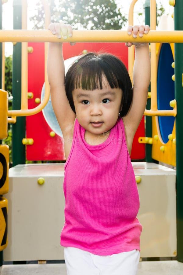 Азиатская маленькая китайская смертная казнь через повешение девушки на горизонтальном баре обезьяны стоковая фотография