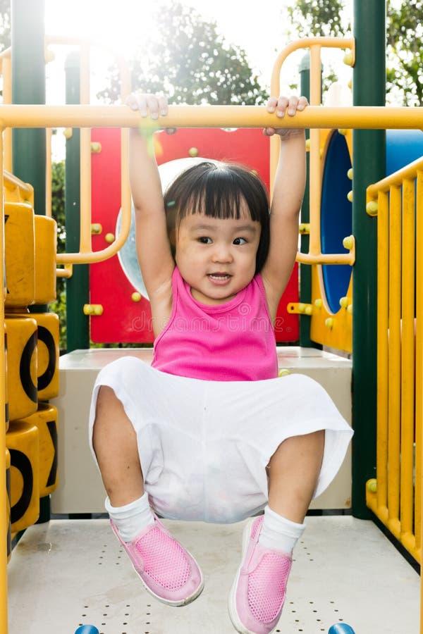 Азиатская маленькая китайская смертная казнь через повешение девушки на горизонтальном баре обезьяны стоковое изображение