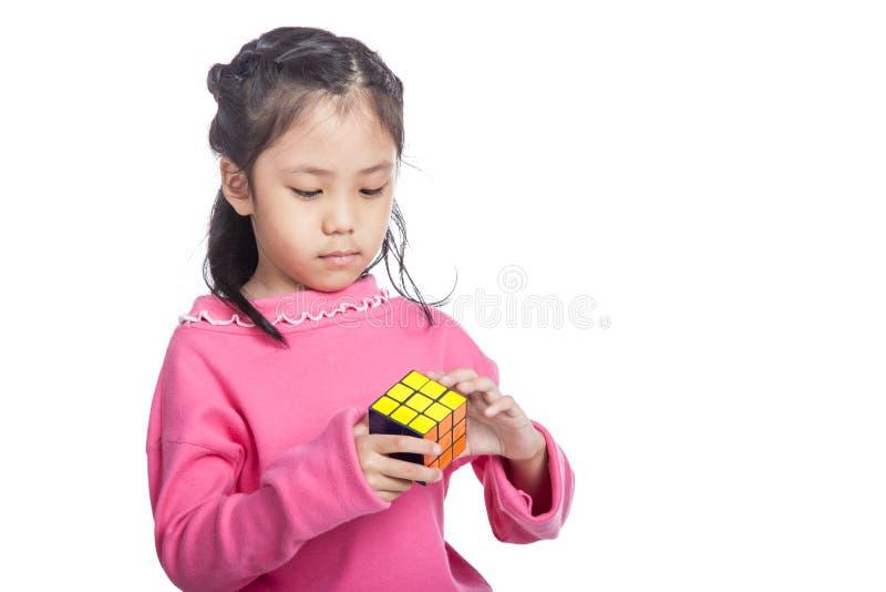 Азиатская маленькая ухищренная девушка разрешает головоломку стоковая фотография rf