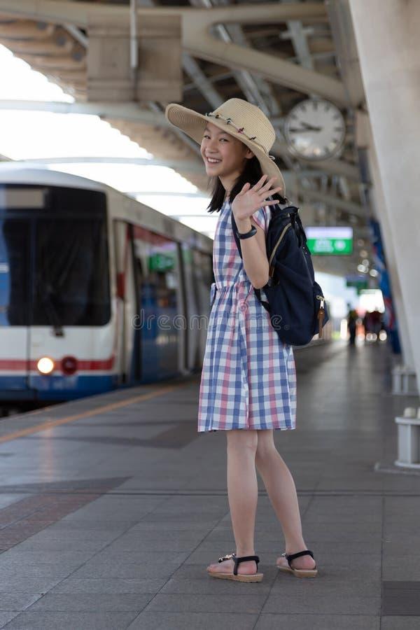 Азиатская милая девушка развевая до свидания перед идет путешествовать на skytrain стоковое фото rf