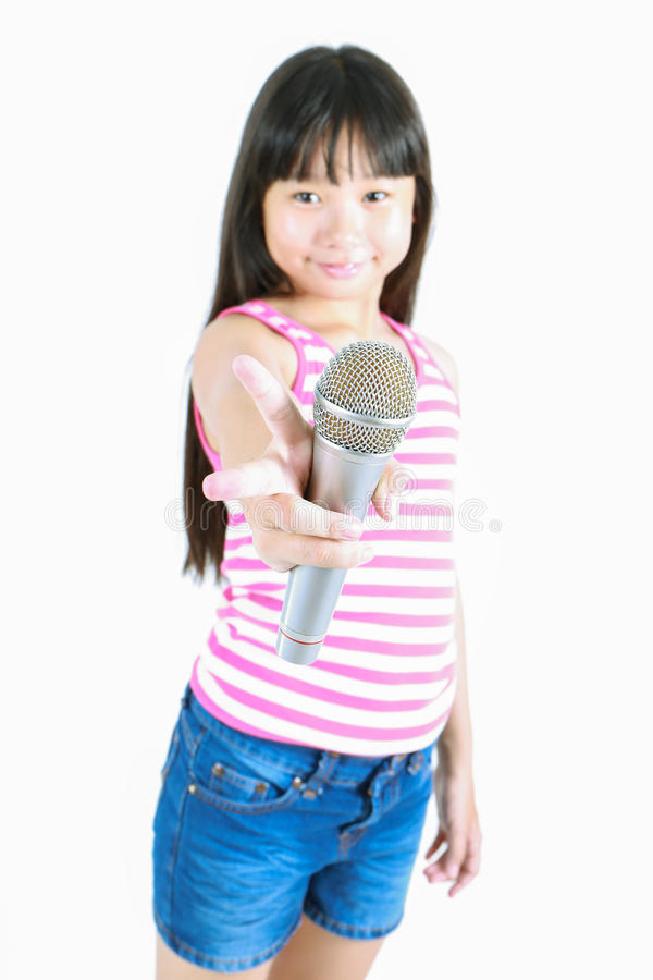 Азиатская милая маленькая девочка поя с микрофоном стоковая фотография