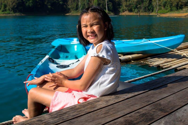 Азиатская милая девушка сидя на парке каяка дока около озера стоковые фото