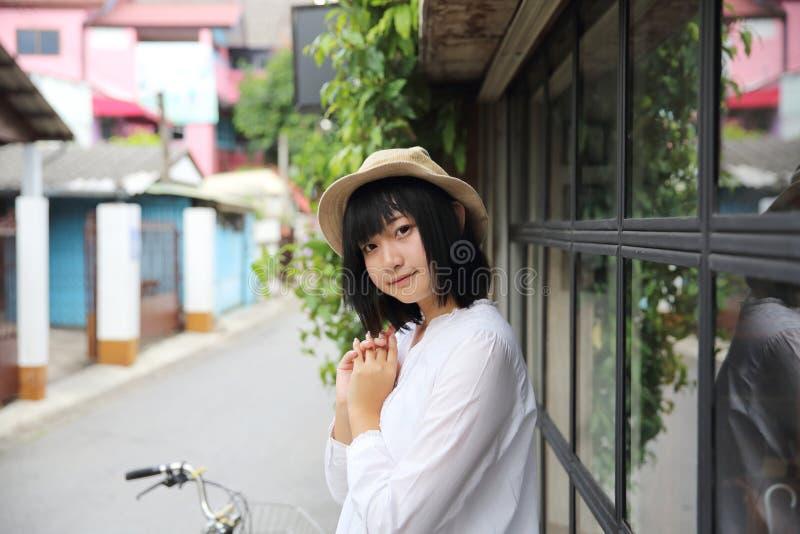 Азиатская молодая женщина думая и смотря портрет с в кофейней стоковые фотографии rf