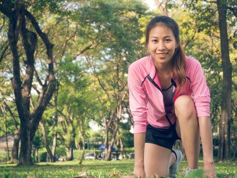 Азиатская молодая женщина на метке, который нужно установить готовый для jogging тренировки построить вверх по ее телу на стекле  стоковое изображение rf